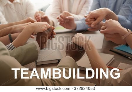 People Holding Hands Together At Table And Text Teambuilding