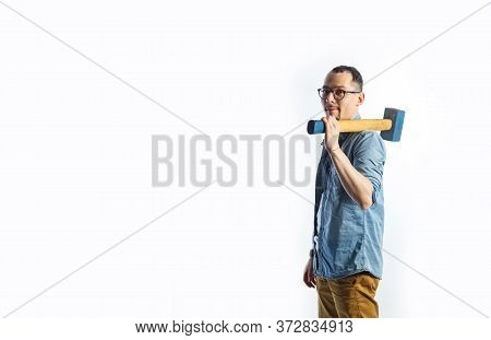 A Man In Blue Shirt Holding A Big Hammer On His Shoulder And Smiling