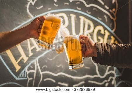 Two People Toasting With Mugs Full Of Chopp, With Background;