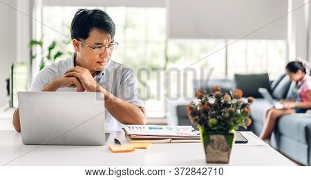 Asian Man Relaxing Using Laptop Computer Working And Video Conference Meeting Chat With His Girl Dau