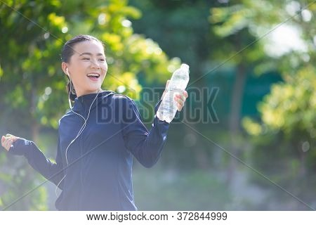 Portrait Of Asian Woman Listening To Music Resting And Drinking Water At Village Park. Cheerful Runn