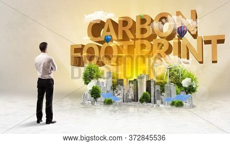 Rear view of a businessman standing in front of CARBON FOOTPRINT inscription, Environmental protection concept