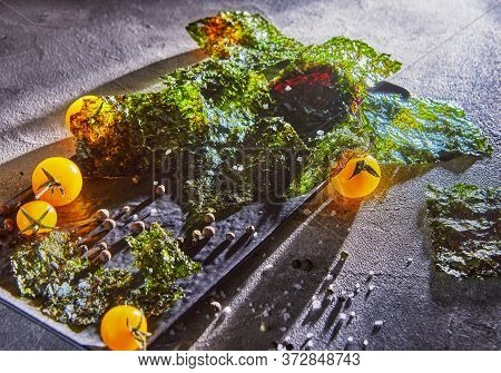 Crispy Nori Seaweed With Cherry Tomatoes And Dark On Gray Concrete. Japanese Food Nori. Dried Sheets