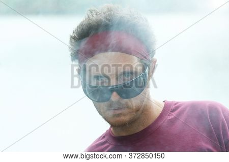 Portrait Of A Fashion Man With Hair Band And Tousled Hair.  Intense Gaze. He Has Blue Eyes And Sungl