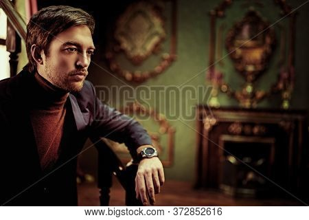 Handsome mature man in elegant formal suit in a luxurious vintage interior. Men's beauty, fashion. Businessman portrait.