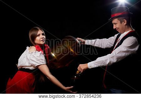 Happy Oktoberfest Couple In National Ethnic Dress With Kegs Of Beer On A Black Background. Girl And