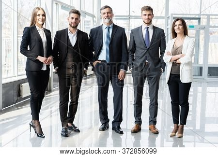 Full Length Confident Business Team Stands In Office.