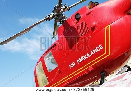 Red Helicopter Of Air Ambulance Isolated On Blue Sky Background. Detail Of The Helicopter Blades. Co