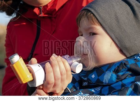 A Small Boy Who Suffering From Illness Bronchial Asthma Getting Treatment With Aerosol Inhaler Outdo