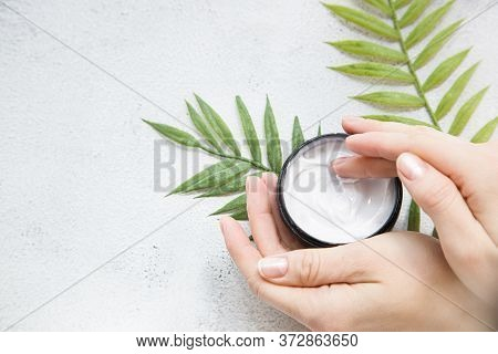 Flatlay. Woman Putting Nutritious Cream On Her Hands On White Background Among Jar Of Cosmetic Cream