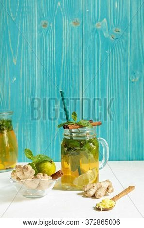 Homemade Lemonade For Improving Metabolism With Lime, Mint And Ginger, In A Glass Cup On An Aquamari