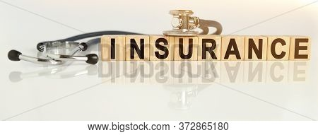 Insurance The Word On Wooden Cubes, Cubes Stand On A Reflective White Surface, On Cubes - A Stethosc