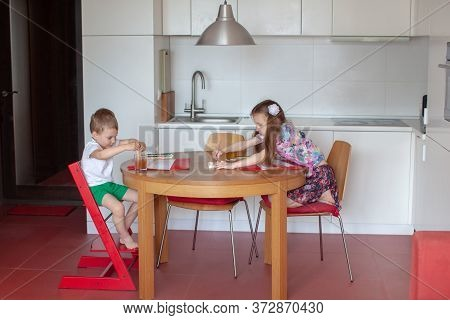 Seven Year Old Girl And Three Year Old Boy Paint In The Kitchen. Modern Home Interior With White And
