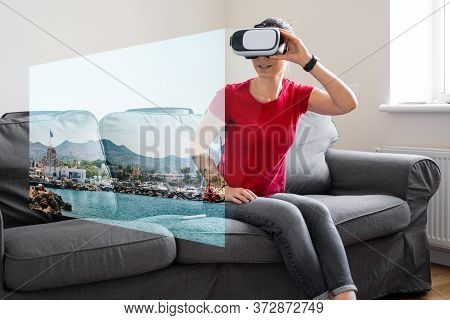 Woman With Vr Glasses Sitting On The Sofa At Home And Watching Online Travel Photo. Vr Booking, Gett