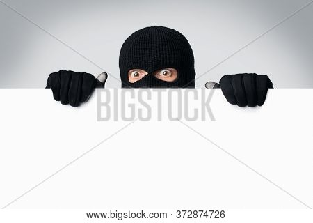 Scared And Surprised Masked Gangster Holding And Looking Out White Blank Board, Isolated Over White