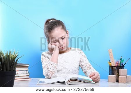 Back To School .happy Cute Industrious Child Is Sitting At A Desk Indoors.the Girl Reads A Book And