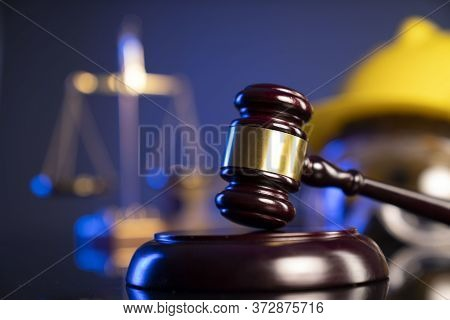 Labour Law And Builiding Law Concept.  Gavel And Yellow Crash Helmet On The Shining Lawer Desk.