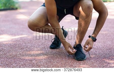 Close Up View Of Black Jogger Tying Laces On His Sports Shoes During His Training Outside. Panorama