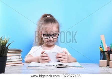 Back To School .happy Cute Industrious Child Is Sitting At A Desk Indoors.uses A Mobile Phone For Le