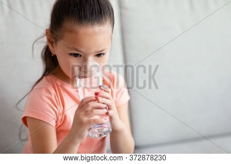 Japanese Kid Girl Drinking Water From Glass Sitting On Sofa At Home. Stay Hydrated Concept. Copy Spa