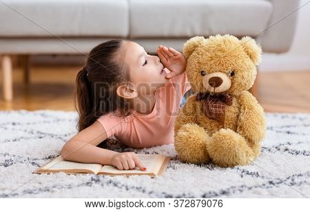 Kids Secrets. Little Asian Girl Reading Book Whispering Sharing Secret With Teddy Bear Playing Lying