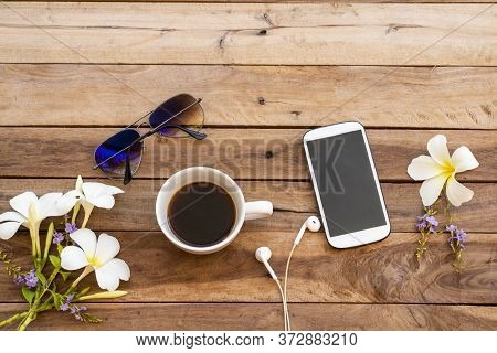 Mobile Phone ,hot Coffee ,sunglasses And White Flowers Frangipani Of Lifestyle Woman Relax Arrangeme