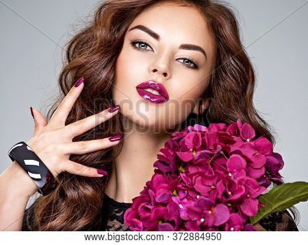 Beautiful  woman with purple make-up of lips and fingernails. Closeup woman's portrait with flowers. Young caucasian gorgeous adult girl with long brown curly hair. Model. Vivid make-up. Sexy female.
