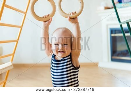 Cute Baby Performs Gymnastic Exercises On A Wooden Home Sports Complex Stairs And Rings. Childrens S