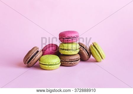 Set Of Tasty French Macaroons On A Pink Background.  Pink, Green And Brown Macaroons.   Place For Te
