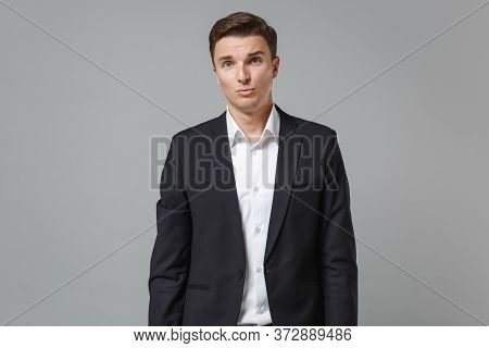Displeased Perplexed Young Business Man In Classic Black Suit Shirt Posing Isolated On Grey Backgrou