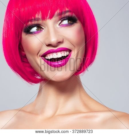Laughing Model with creative colored bob hairstyle.  Beautiful cheerful fashion woman with pink lipstick. Fun fashion model with bright make-up. Closeup beauty portrait.