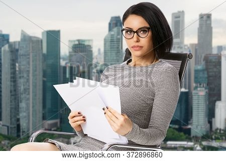 Pensive Young Business Woman In Glasses Sitting On Chair With Paper Documents Over Singapore City Ba