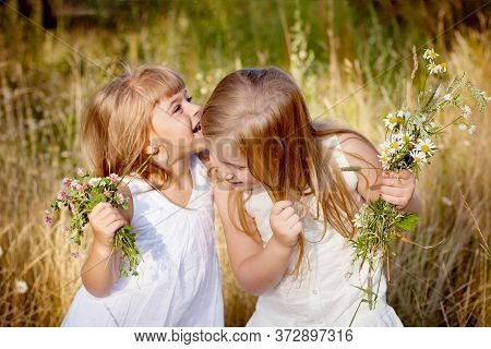 Two Girls Friends In The Meadow Whisper In Your Ear. They Have Wildflowers In Their Hands.