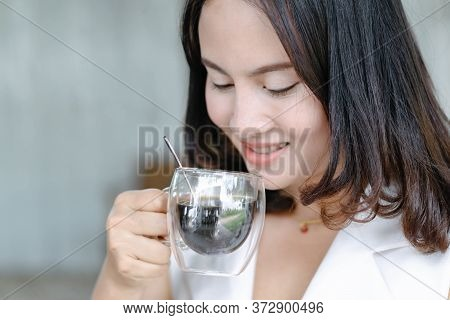 Close Up Woman Drinking Hot Americano Coffee From Glass With Light In The Morning, Selective Focus