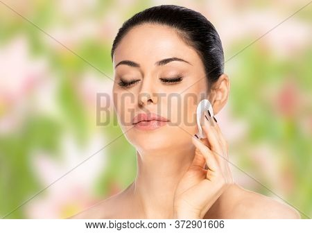 Beautiful Brunette Woman With Cotton Pad Over Blurred Background. Health And Beauty Concept