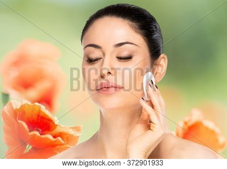 Beautiful Brunette Woman With Cotton Pad Over Flowered Background. Beauty Skin Care Concept.