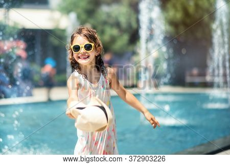 Loving Life. Cheerful Little Girl In Summer Light Dress And Yellow Sunglasses Having Fun And Playing