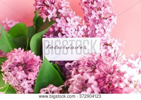Inscription Congratulations On Spanish On A White Gift Card In A Beautiful Bouquet Of Lilac Flowers