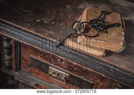 Old Vintage Keys On An Old Battered Book, Antique Wooden Background. The Concept Of Mystery And Disc