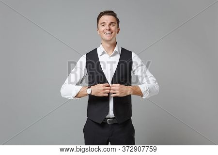 Smiling Young Business Man In Classic Black Waistcoat Shirt Posing Isolated On Grey Wall Background