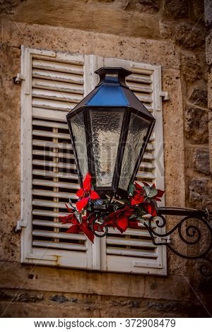 Old Lantern, Medieval Street Light With Red Flowers In The Street On The Light Background In Budva M