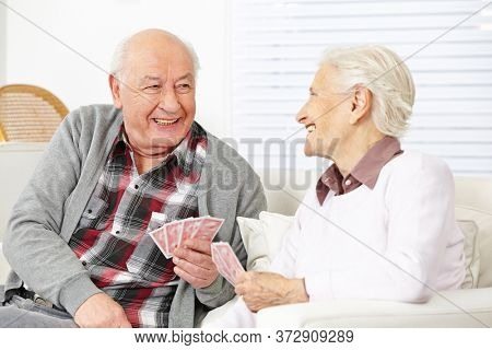 Two happy seniors laughing playing cards together in the living room