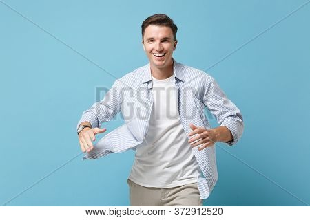 Smiling Young Man Guy 20s In Casual Shirt Posing Isolated On Pastel Blue Background Studio Portrait.