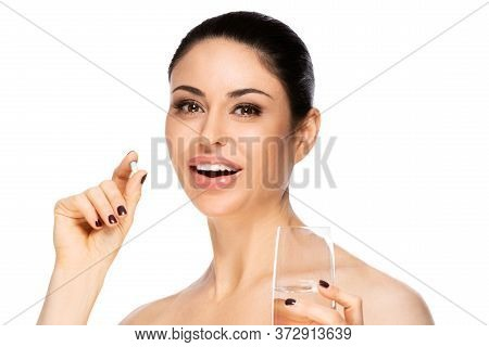 Closeup Portrait Of Beautiful Woman Taking Pills, Isolated. Healthcare And Medical Concept