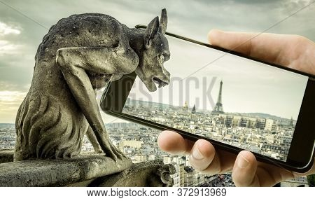Gargoyle On Cathedral Of Notre Dame De Paris Looks At Eiffel Tower In Mobile Or Cell Phone, Paris, F