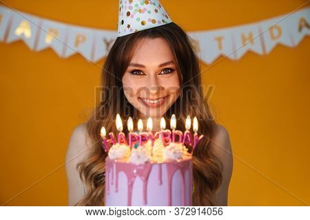 Image of delighted young woman in party cone showing birthday torte with candles isolated over yellow background