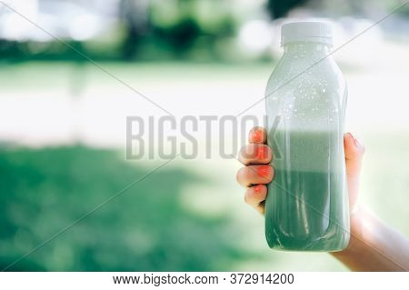 Closeup Of Womans Hand With Bright Orange Manicure Holding Takeout Container Of Green Tea Laminaria