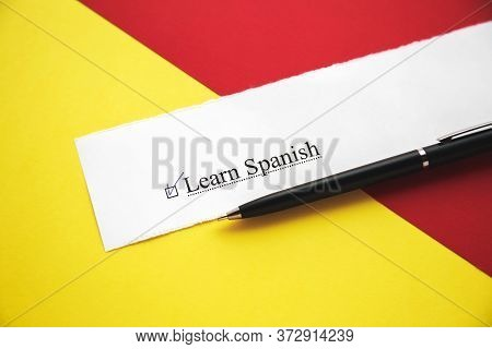 A Piece Of Paper With The Inscription Learn Spanish From To Do List With A Tick On A Red-yellow Back