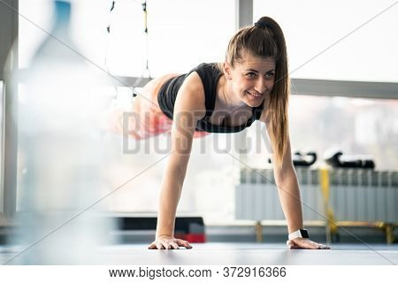 Fit pretty woman doing planks in gym using gym equipment