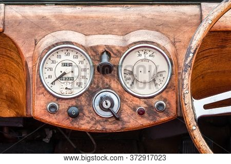 Wooden Steering Wheel And Dashboard Interior Of A Vintage Automobile